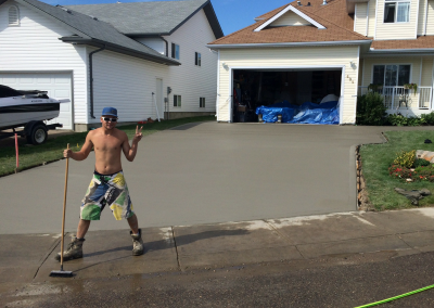 Concrete Finisher Cleaning Up After A Concrete Driveway Pour
